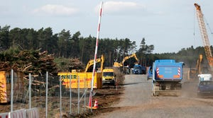 In this Monday, March 16, 2020 photo machines work at a construction site of the planned new Tesla Gigafactory in Gruenheide near Berlin, Germany.