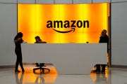 """In this Feb. 14, 2019 file photo, people stand in the lobby for Amazon offices in New York.  The United States for the first time added five of Amazon's overseas operations to its list of """"notorious markets"""" where pirated goods are sold.   Trade Representative on Wednesday, April 29, 2020 added the Amazon domains in Canada, France, Germany, India and the United Kingdom to its annual blacklist."""