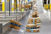 In this Dec. 17, 2019, file photo, Amazon packages move along a conveyor at an Amazon warehouse facility in Goodyear, Ariz.