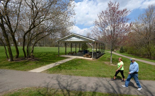 Ed Maciejewski and his wife, Cindy, 37-year residents of Bruce Township, pass The Melton Family Pavillion, Est. 2011, at the Bruce Township Park.