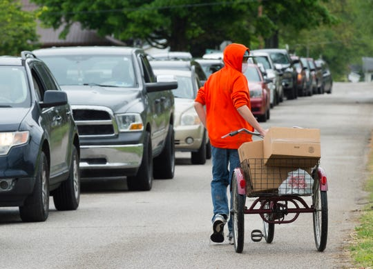 Andre Glein, 15, walks down Shadewood Avenue with meal kits distributed by the Evansville Vanderburgh School Corporation in partnership with AmeriQual Group as a line of cars wait to pick up food from Glenwood Leadership Academy Wednesday afternoon, April 29, 2020.