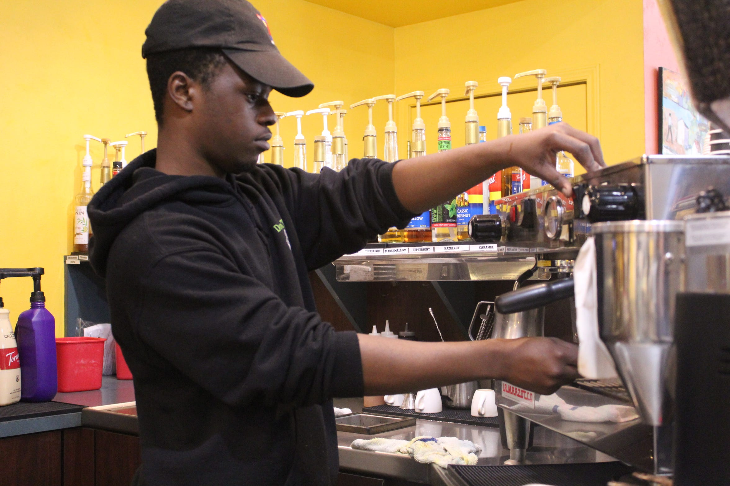 Down Thyme Cafe employee Joe Jones makes a coffee drink Wednesday at the downtown Fremont business. Jones said there is not nearly the same amount of foot traffic coming into the business with the coronavirus-related restrictions put in place.