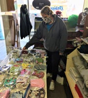 Marie Darr adds some face masks to the  merchandise available at Designs by Marie, 133 W Water Street. The clear glass protects both her and her customers when they shop.