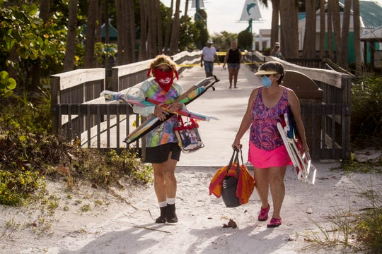 North Fort Myers residents, Kathy Murdoch, left, and Myra Gross head onto Bowditch Point Park on the north end of Fort Myers Beach on Wednesday, April 29, 2020 morning. Lee County opened up the beaches it manages Wednesday to the public after they were closed because of the COVID-19 Pandemic. The beach that is managed by the town of Fort Myers Beach which is from Crescent Beach south is still only open to Fort Myers Beach residents from 7-10 a.m. for exercise. They were the few people who had masks on.