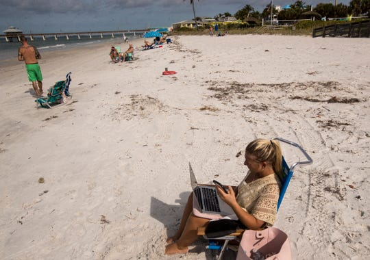 Patricia Antonelli works from her beach chair at Crescent Beach Park on Fort Myers Beach on Wednesday, April 29, 2020 morning. Lee County opened up the beaches it manages Wednesday to the public after they were closed because of the COVID-19 Pandemic. The beach that is managed by the town of Fort Myers Beach which is from Crescent Beach south is still only open to Fort Myers Beach residents from 7-10 a.m. for exercise.