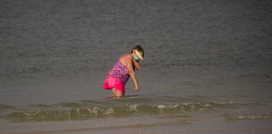 North Fort Myers resident Myra Gross enjoys the Gulf of Mexico at Bowditch Point Park on the north end of Fort Myers Beach on Wednesday, April 29, 2020 morning. Lee County opened up the beaches it manages Wednesday to the public after they were closed because of the COVID-19 Pandemic. The beach that is managed by the town of Fort Myers Beach which is from Crescent Beach south is still only open to Fort Myers Beach residents from 7-10 a.m. for exercise. She was one of the few people who had a mask on.