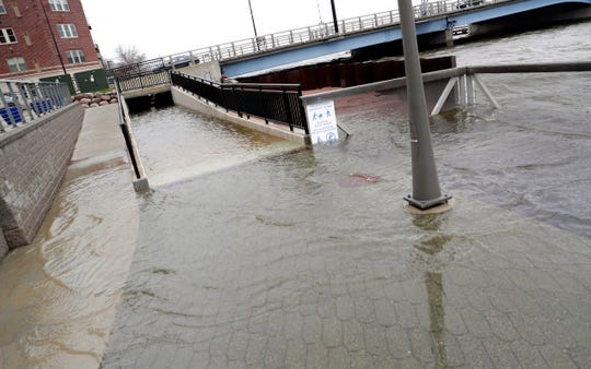 Strong winds on the bay cause flooding on CityDeck near the Fox River on April 29, 2020, in Green Bay, Wis.