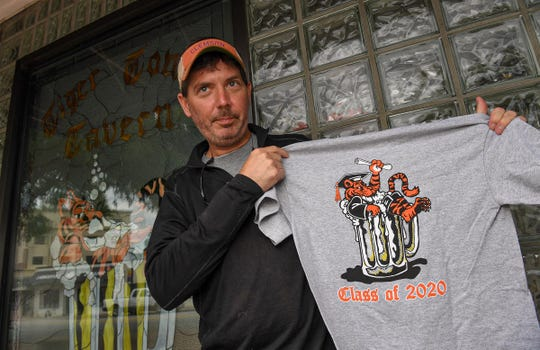 Cameron Farish, co-owner of Tiger Town Tavern in Clemson, shows a T-shirt he made to sell graduates through the Tiger Town Graphics website, since Clemson University's campus is closed from the COVID-19 pandemic.