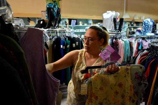 Shannon Thompson looks through clothing items at the Northern Treasure thrift store on Monday, April 27, 2020 in Roundup, Mont. As shutdowns are eased in parts of America, some of the quickest to reopen are rural states. (AP Photo/Matthew Brown)