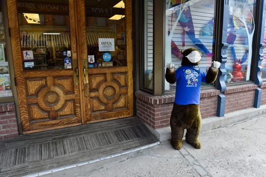 A PPE-clad stuffed bear greets patrons at the Lasso the Moon toy store Monday, April 27, 2020, in Helena, Mont. (Thom Bridge/Independent Record via AP)