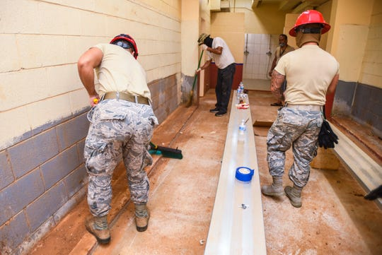 """Guam National Air Guard 254th Red Horse Squadron personnel and Department of Parks and Recreation employees work together to renovate one of the locker rooms at the Paseo Stadium in Hagåtña on Wednesday, April 29, 2020. The Guard members, along with other Government of Guam agencies and nonprofit organizations, are coordinating their efforts in """"Operation Safe Haven"""" to prepare the venue as a temporary shelter for the island's homeless population during the coronavirus pandemic."""