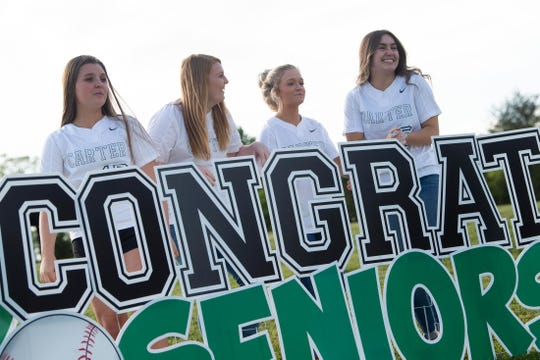 From left, Carter High School softball seniors Alyssa Fawver, Hannah Branam, Makinsey Russell and Emma Cannon stand behind an elaborate display during a parade at Carter Park on Tuesday, April 28, 2020 to recognize and celebrate the seniors on the baseball and softball teams. The seniors had their season cut short because of the coronavirus.