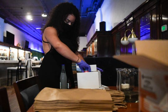 Server at Saphire. Olivia Lee, demonstrates how to-go drinks are prepared, at the restaurant and bar on Gay Street, Wednesday, April 29, 2020. Owner Aaron Thompson has decided not to fully open up until June, despite some coronavirus restrictions being lifted.