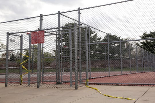 Caution tape used to block the entrances to the tennis courts at West Lafayette Elementary School blows in the wind, Tuesday, April 28, 2020 in West Lafayette.
