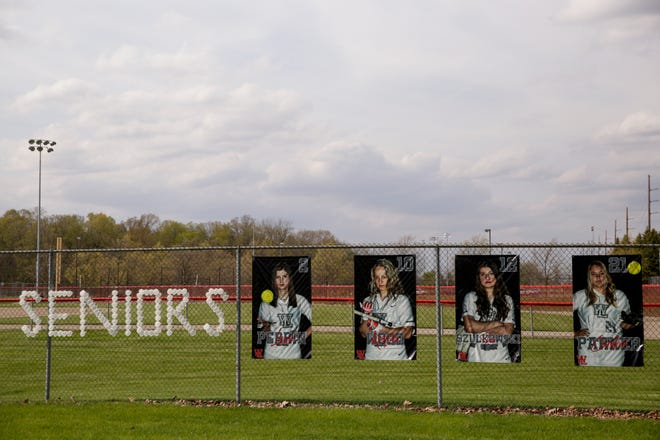 """""""Seniors"""" is spelled out of cups in the right field fencing next to pictures of senior softball players at the West Lafayette High School Sports Complex, Tuesday, April 28, 2020 in West Lafayette."""