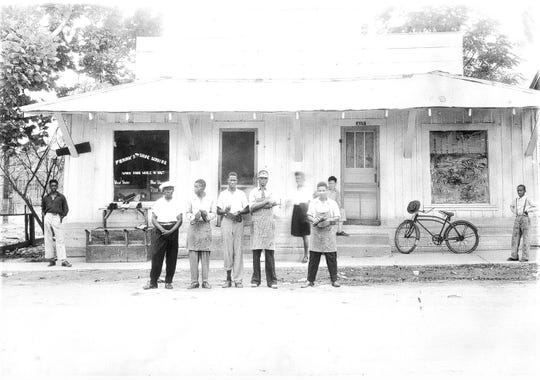 In December 1964 , Frank Morris (Center, with Apron) was murdered when his Ferriday, Louisiana, shoe shop was torched while he was inside.