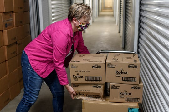 Lysne Tait, executive director of Helping Women Period, stacks boxes of menstrual pads for a client at a storage facility on Wednesday, April 29, 2020, in Lansing. Helping Women Period offers free feminine hygiene products to at-risk and homeless women.