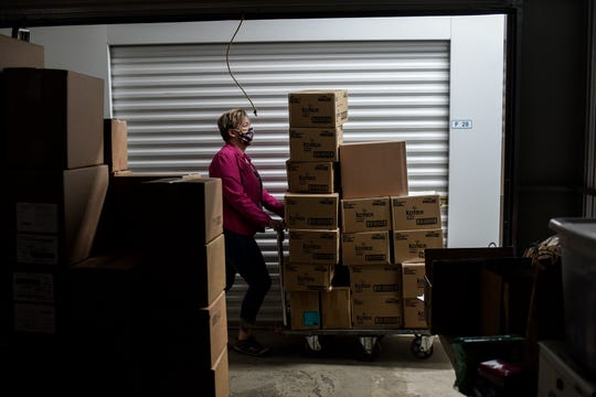 Lysne Tait, executive director of Helping Women Period, pushes a cart of menstrual products for a client to pick up at a storage facility on Wednesday, April 29, 2020, in Lansing. Helping Women Period offers free feminine hygiene products to at-risk and homeless women.