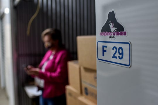 Lysne Tait, executive director of Helping Women Period, checks her phone in a storage unit on Wednesday, April 29, 2020, in Lansing. Helping Women Period offers free feminine hygiene products to at-risk and homeless women.
