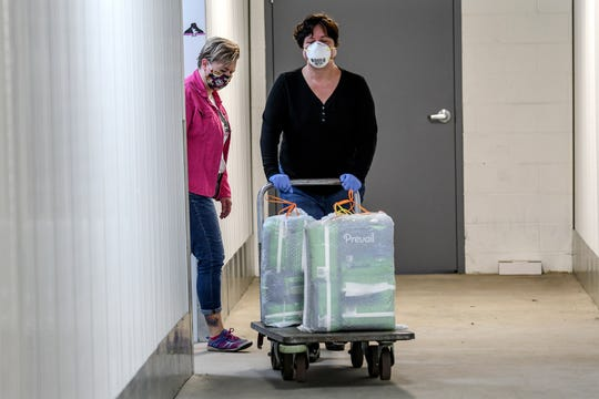 At right, Kristen Frazer, of Livity Inc., carts out some adult diapers that Lysne Tait, executive director of Helping Women Period, left, had at a storage facility on Wednesday, April 29, 2020, in Lansing. Helping Women Period offers free feminine hygiene products to at-risk and homeless women.