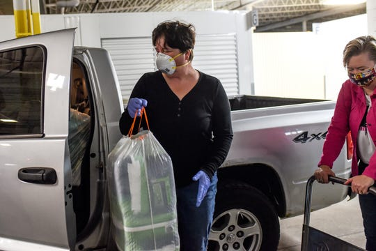 At left, Kristen Frazer, of Livity Inc., loads adult diapers that Lysne Tait, executive director of Helping Women Period, right, gave to her at a storage facility on Wednesday, April 29, 2020, in Lansing. Helping Women Period offers free feminine hygiene products to at-risk and homeless women.