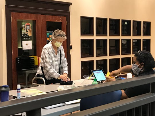 Charlene Wilson signs in to vote at the Marion County Board of Elections on Tuesday. She said she sent a request in the mail for an absentee ballot, but did not receive one. There was limited in-person voting at county boards of elections in Ohio on Tuesday.