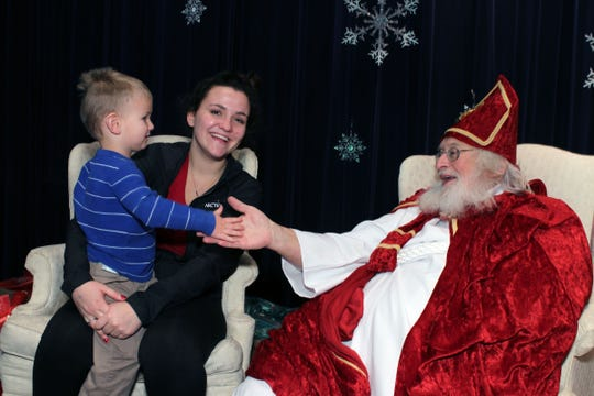 In this 2015 photo, Owen Green of Oconomowoc gives five to St Nick, played by Bill Woolley of Pewaukee, while his aunt Sami Jackson of Oconomowoc, watches.