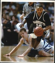 Marquette's Tony Miller breaks yet another Kentucky press as he races past fallen Wildcat Jared Prickett in an NCAA Southeast Regional game in St. Petersburg, Florida, in 1994. The Warriors advanced with a 75-63 victory.