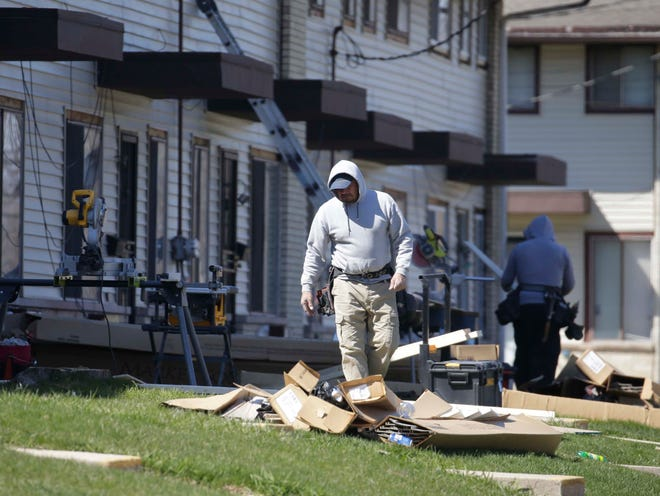Construction workers, some wearing masks, renovating properties on North 84th Street that are managed by Berrada Properties Management.