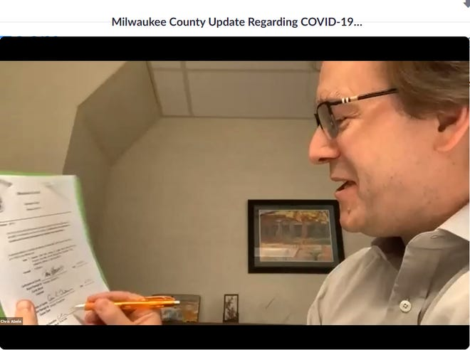 Outgoing Milwaukee County Executive Chris Abele signs an ordinance committing the county to achieving racial equity during a virtual news conference Wednesday. The news conference took place online due to the coronavirus pandemic.