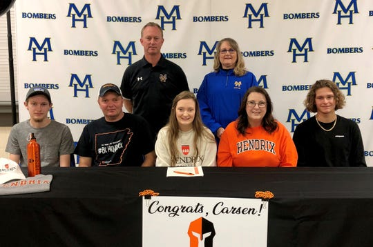 Mountain Home's Carsen Cotter (front row, center) signed Wednesday a National Letter of Intent to swim at Hendrix College in Conway. Pictured with Cotter at her signing are: (front, from left) brother Chance Cotter, father Curt Cotter, mother Michelle Cotter, brother Camden Cotter; (back row) MHHS athletic director Mitch Huskey, and MHHS swim coach Kathy Wham.