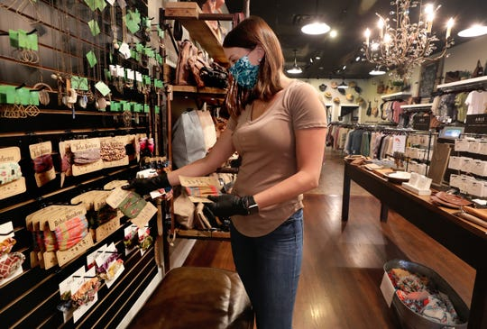 Trendy Pieces employee Meredith McDowell restocks Boho Bandeaus, that some people use as a face mask on the shelves of the store on on Wednesday, April 29, 2020, the first day retail stores were allowed to have customers inside their store, due to the COVID-19 shutdowns.