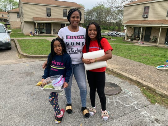 Cynthia Davis and her two daughters, Delilah, 7, left, and De'Andrea, 10, show the food donations they received at home from FrankTown Open Hearts agency, which serves inner-city youth in Franklin, Tenn.