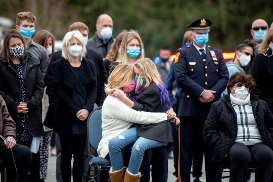 Danielle Walker and her daughter, Demi, are surrounded by family and loved ones, during a service in memory of Walker's husband Gary Walker, 53, a longtime Bloomingdale police officer and firefighter for Oakland, outside of Bloomingdale Borough Hall on April 29, 2020. Walker died due to complications from Covid-19.