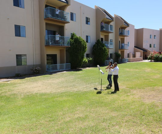 Amalia Kelter Zeitlin and Daniel Vega-Albela, with Camerata del Sol Chamber Orchestra, perform on the lawn of Good Samaritan Society - Las Cruces Village, Wednesday, April 29, 2020, as residents watch from their balconies.