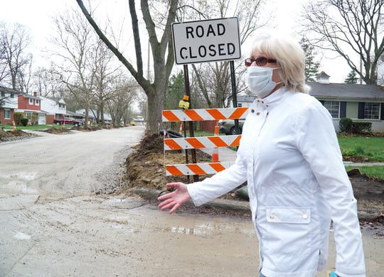 Ann Zaron walks along a street near her Farmington Hills home. The city has been cutting down large, healthy trees in the area as it works on roads and curbs. She's worried that they're cutting too many.