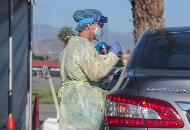 A health care professional tests a Coachella Valley resident for Covid-19 at the drive-up testing site at the Riverside County Fairgrounds in Indio, April 29, 2020.