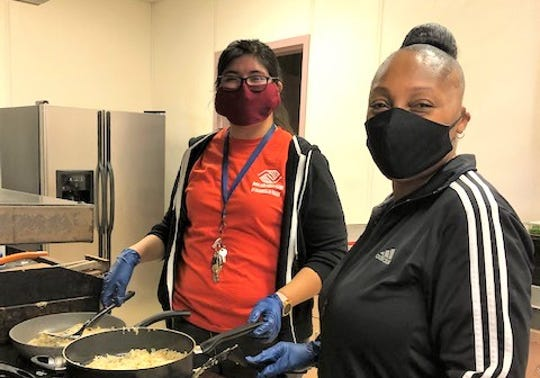Tracy Reed, unit director (Indio), and Mayra DuBose, assistant unit director (La Quinta), help with food preparation.