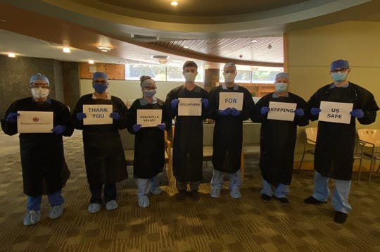 Workers wear isolation gowns that were made by the CV Mask Project, an effort spearheaded by actress Lucie Arnaz.