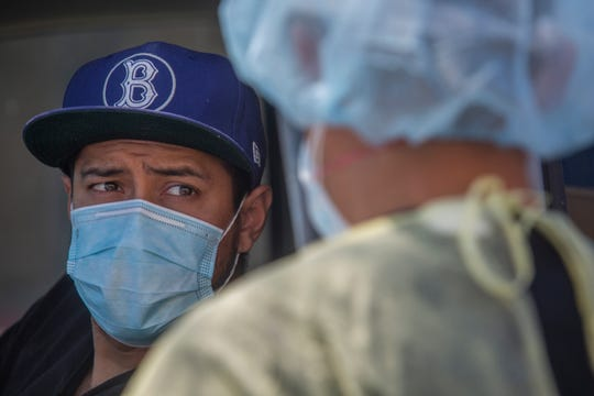 DO NOT USE DO NOT USE Registered Nurse Daniel Arzate administers a COVID-19 test to Mecca resident Steve Herrera at the Centro Medico Cathedral City health clinic on April 28, 2020.