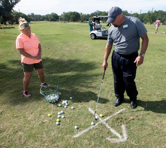 Adrian Stills, the golf pro at Osceola Golf Course, practices social distancing protocols while teaching the game to Bridget Wakeman on Tuesday, April 28, 2020.