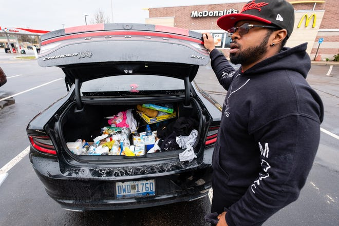 Terrell Kelly, a local personal trainer, shows boxes of food in the trunk of his car Wednesday, April 29, 2020, in Port Huron. Kelly has been using his stimulus money to distribute non-perishable food and hygiene items to people in need in the area.