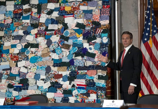 Gov. Andrew Cuomo displayed a mural of mask donated to him during a coronavirus briefing at the state Capitol on April 29, 2020.