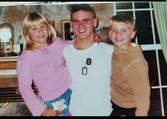 Anthony Machulcz (center) holds his siblings, twins Hannah and Jacob Machulcz. In this photo, Anthony had returned home from boot camp. He's been serving in the Navy nearly 20 years, and Jacob (right) has followed in his footsteps.