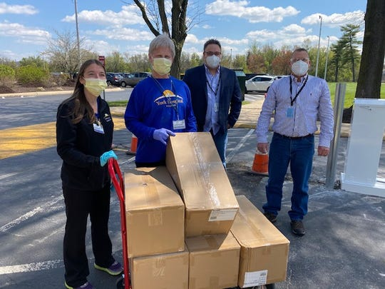 In this submitted photo from April 15, York County Prison Warden Clair Doll, center, and John McCoy, facility manager, right, donate 1,000 N95 respirators to WellSpan Health.
