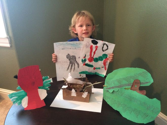 """Monarch Charter School kindergartner Micah Young, 5, shows off some of the crafts he made during the Shasta Family YMCA's """"Storytime and Craft with Carol"""" class in Zoom."""