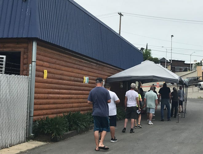 Customers line up to wait to get into R&R Meats & Seafood on Wednesday, April 29, 2020. The store in Redding limits the number of people in inside.
