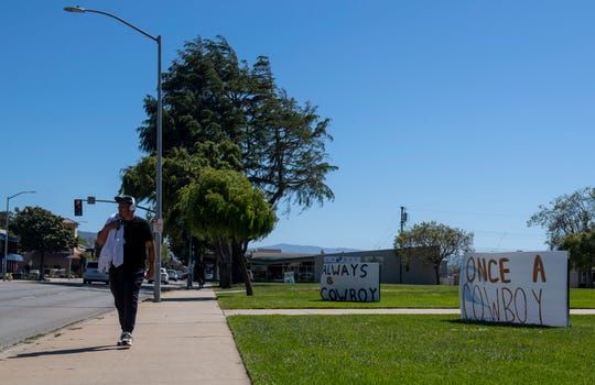 A Salinas resident walks in front of two signs that were placed by several Salinas High School teachers to spread positivity to all of their students who will be learning at home for the remainder of the school year due to the COVID-19 pandemic. This photo was taken on Tuesday, April 28, 2020.