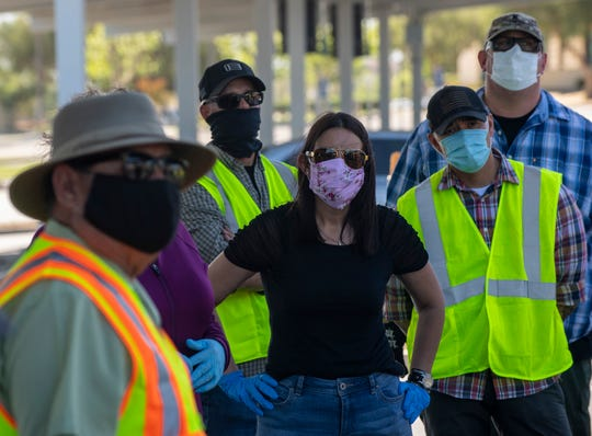 Anna M. Velazques, Soledad city council member stands in a powerful pose as she listens to instructions before the start of the South County Food Distribution event in Soledad, Calif, on Friday, April 24, 2020.