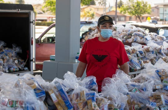 A woman wearing a red United Farm Workers shirt stands behind a table full of food bags on Friday, April 24, 2020.